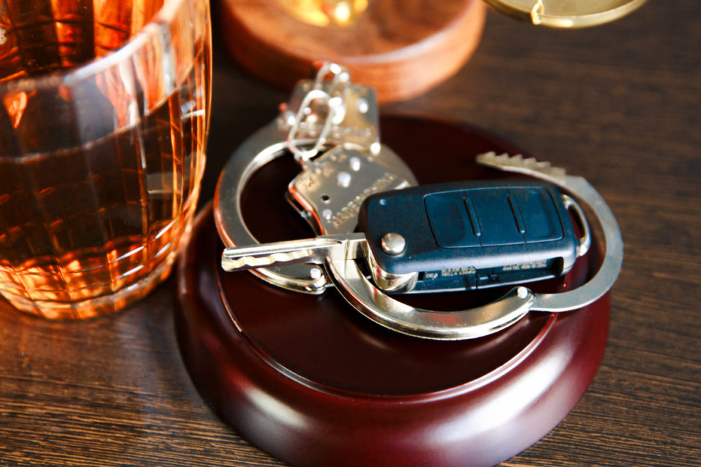 Law hammer, alcohol and car keys on wooden table, dark background